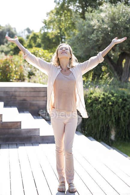 Felice donna elegante con le braccia tese a piedi in giardino — Foto stock
