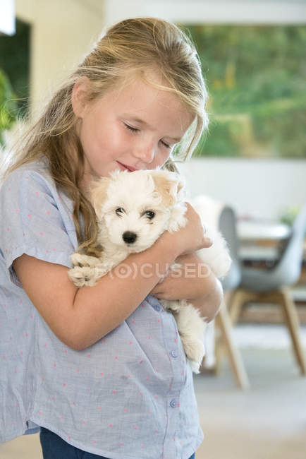 Portrait of cute little girl holding puppy — Stock Photo
