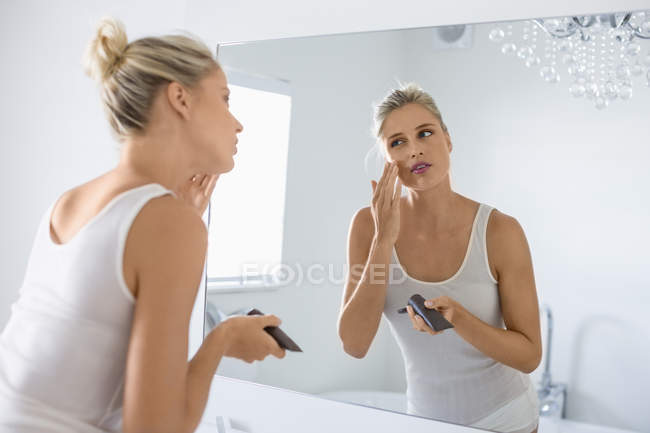 Blond young woman applying moisturizer on face in bathroom — Stock Photo