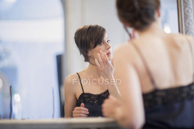 Woman applying anti-aging cream on face in front of mirror — Stock Photo