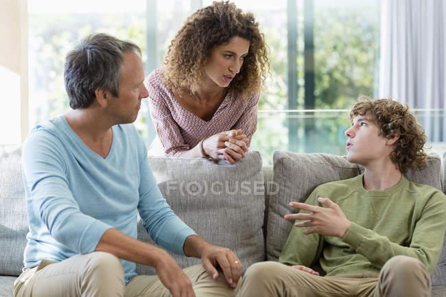 Familia descansando y conversando en la sala de estar en casa - foto de stock