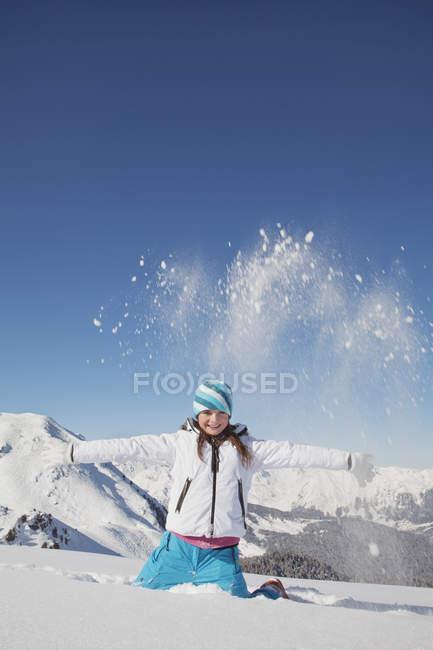 Porträt eines Mädchens in Skikleidung, das in den Winterbergen Schnee in die Luft wirft — Stockfoto