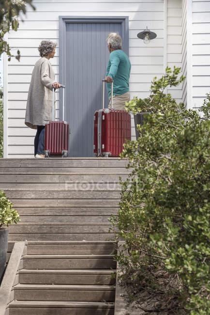 Coppia anziana con valigie in attesa alla porta d'ingresso — Foto stock