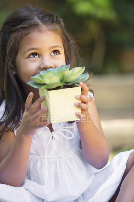 Cute little girl holding potted plant and looking up outdoors — Stock Photo