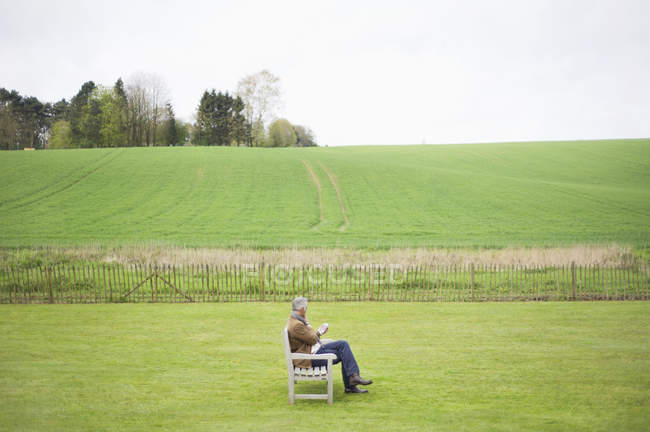 Man sitting on wooden bench and using mobile phone in green field — Stock Photo