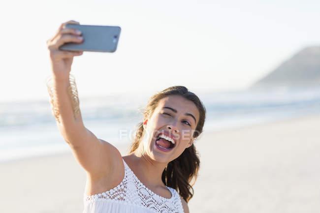 Espiègle jeune femme prenant selfie smartphone sur la plage — Photo de stock