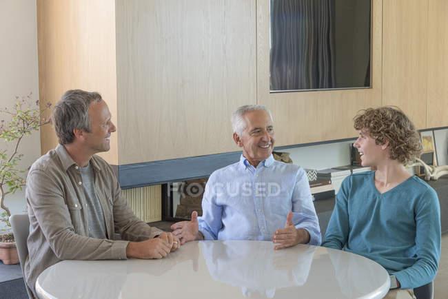 Uomo maggiore felice con il figlio e nipote seduto e parlare al tavolo nel soggiorno — Foto stock