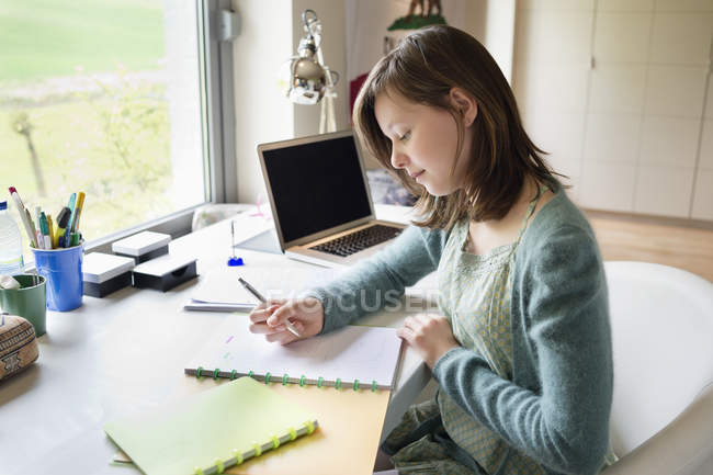 Focused teenage girl studying at desk at home — Stock Photo