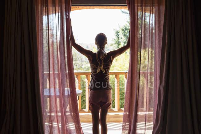 Улыбающаяся женщина открывает занавески в комнате — стоковое фото