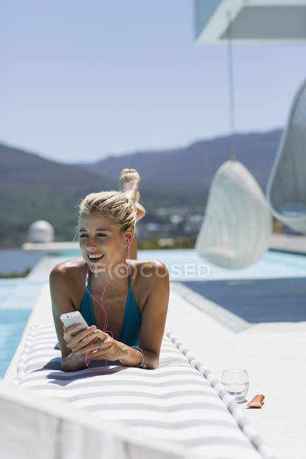 Relajado mujer joven escuchando música con el smartphone en junto a la piscina - foto de stock