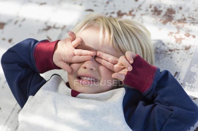 Menino brincalhão deitado e cobrindo os olhos com as mãos — Fotografia de Stock