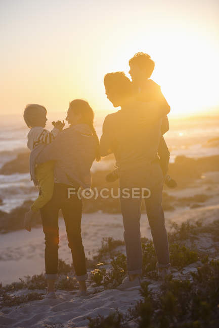 Rear view of happy family standing on beach at sunset and looking at view — Stock Photo