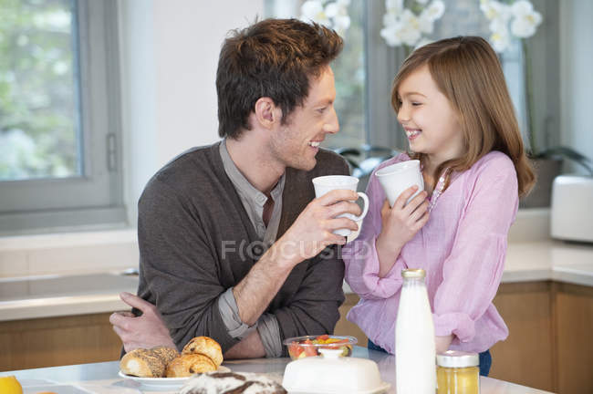 Man drinking tea with daughter in kitchen — Stock Photo