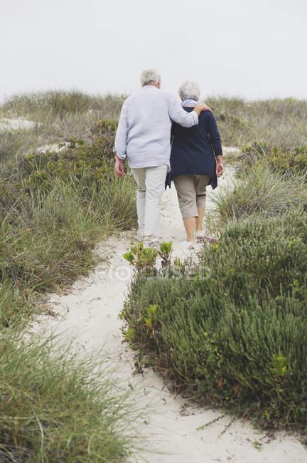 Rear view of senior couple walking on coast — Stock Photo