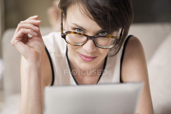 Portrait of woman in glasses holding digital tablet and looking at camera — Stock Photo