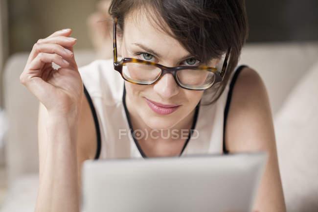 Portrait de femme dans des lunettes tenant tablette numérique et regardant la caméra — Photo de stock