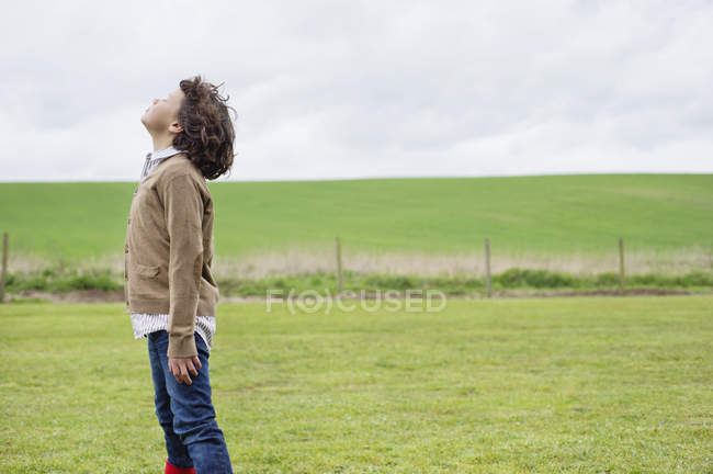 Boy daydreaming in green field under cloudy sky — Stock Photo