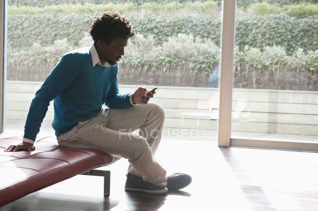 Man text messaging with mobile phone on bench in room — Stock Photo