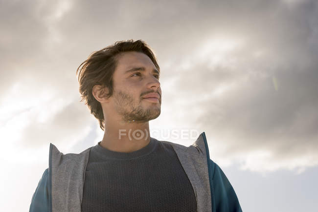 Portrait of young man looking away against cloudy sky — Stock Photo