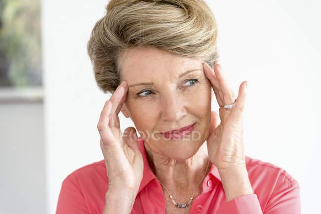 Крупным планом счастлив старший женщины с головой в руках — стоковое фото