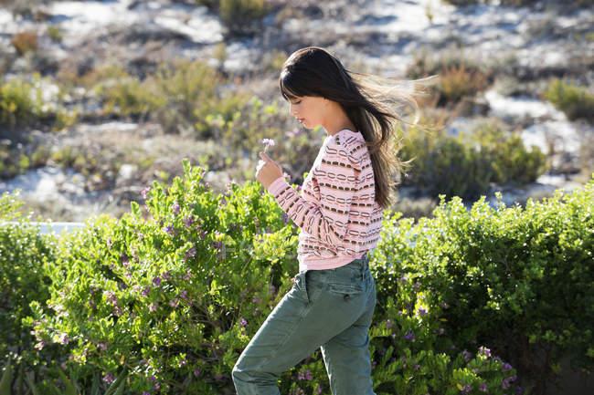 Mulher segurando flor enquanto caminha em vegetação verde — Fotografia de Stock