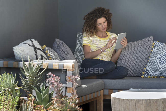 Woman sitting on couch at home and using digital tablet — Stock Photo