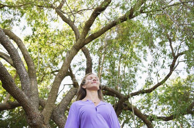 Молодая расслабленная женщина стоит под зеленым деревом — стоковое фото