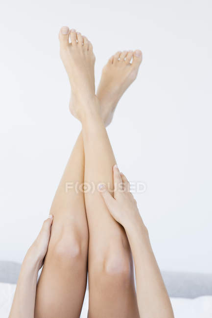 Close-up of female hands touching legs on white background — Stock Photo