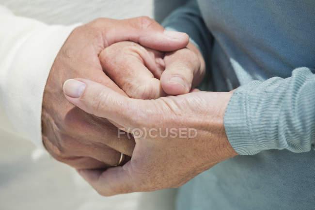 Крупный план влюбленной пары, держащейся за руки — стоковое фото