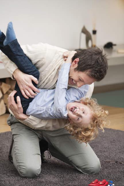 Веселий чоловік грає з сином на килимовій доріжці в домашніх умовах — стокове фото