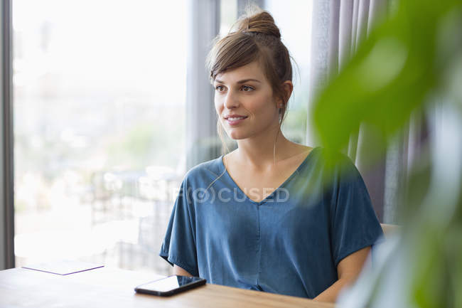 Close-up of smiling young woman sitting at table next to window — Stock Photo