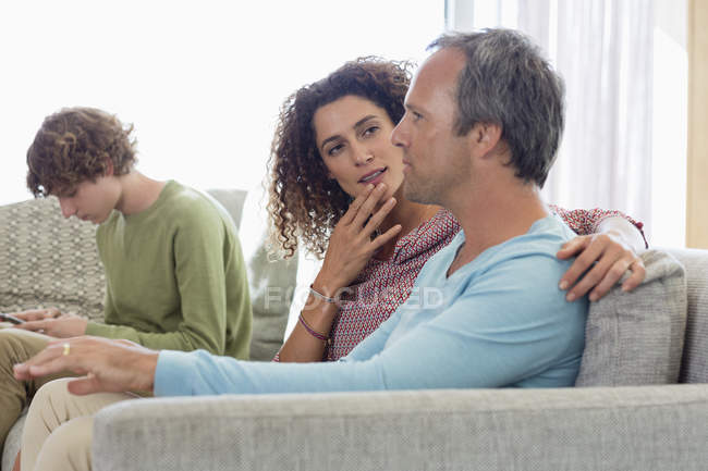 Пара, сидя на диване и разговор с сыном, с помощью мобильного телефона на фоне в гостиной дома — стоковое фото