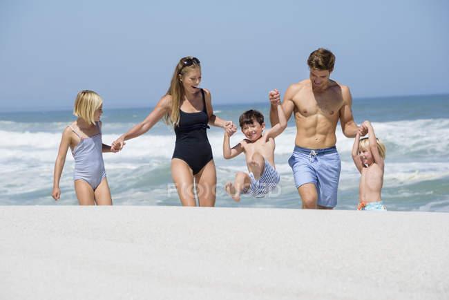 Famiglia felice che cammina sulla spiaggia mano nella mano e scherzare — Foto stock
