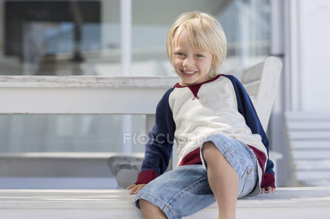 Portrait of happy little boy with blonde hair smiling outdoors — Stock Photo