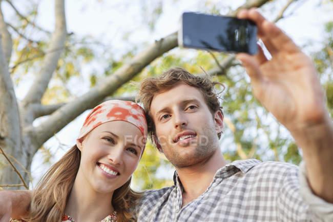 Jeune couple selfie prise avec le téléphone mobile dans le parc — Photo de stock