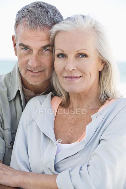 Portrait of smiling senior couple on beach — Stock Photo