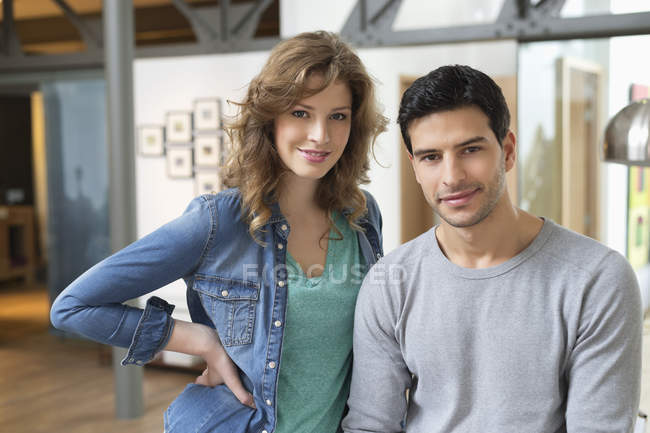 Portrait of smiling young couple looking at camera in room — Stock Photo