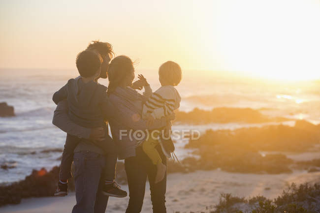 Happy family standing on beach at sunset and looking at view — Stock Photo