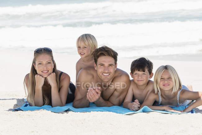Портрет щаслива родина, лежачи на ковдру на пляжі — стокове фото