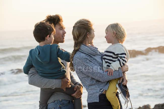 Glückliche Familie am Strand bei Sonnenuntergang — Stockfoto