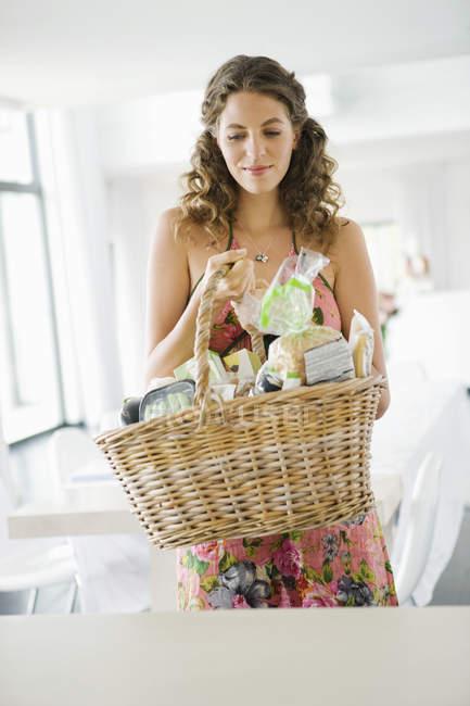 Frau hält Korb mit Essen in der Küche — Stockfoto