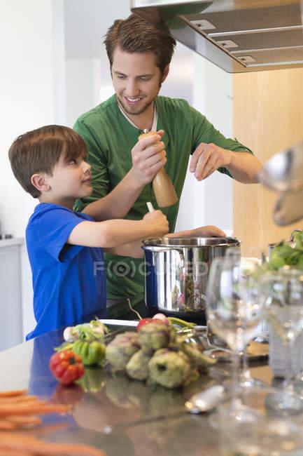 Маленький хлопчик допомагаючи батькові в кухні — стокове фото