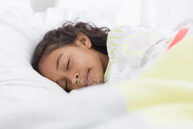Милая маленькая девочка спит на кровати — стоковое фото