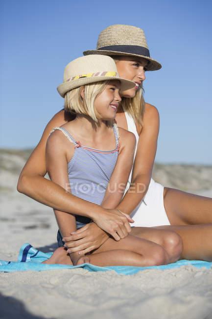 Портрет счастливой женщины и дочери в шляпах, сидящих на пляже — стоковое фото
