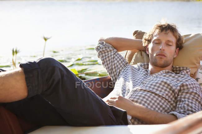 Расслабленный молодой человек спит в лодке на озере в сельской местности — стоковое фото