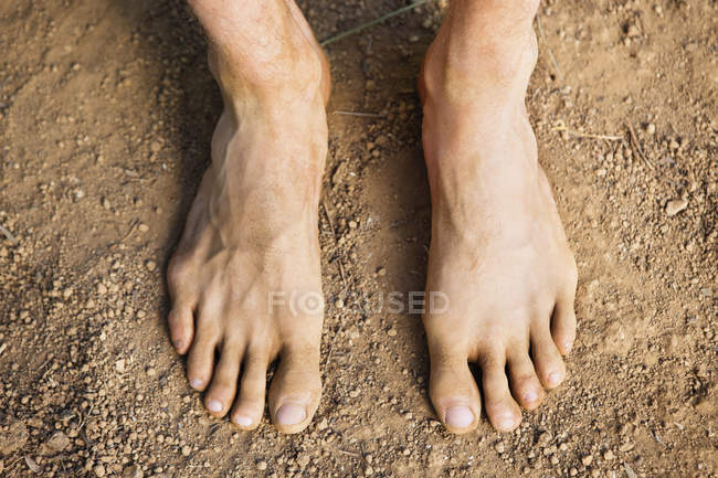 Close-up of male feet standing on ground — Stock Photo