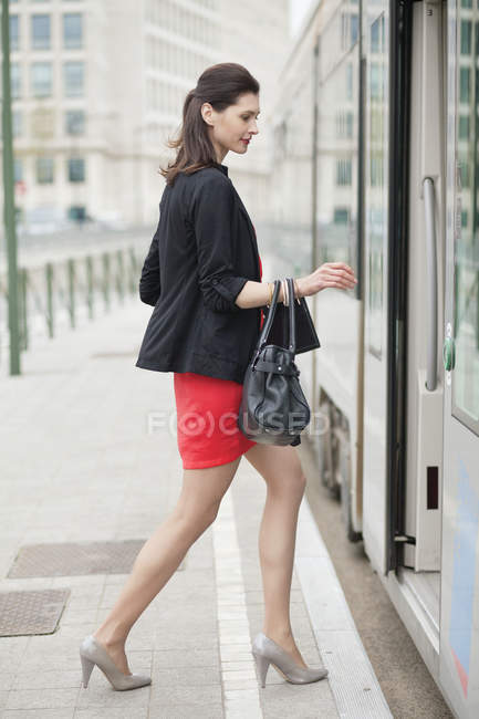 Confident elegant woman getting in bus in city — Stock Photo