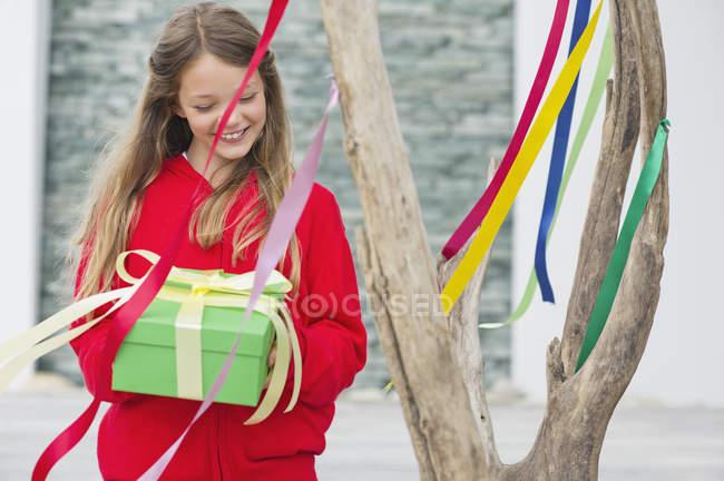 Усміхаючись дівчинка тримає подарунковій коробці поблизу дерево з барвистими стрічками — стокове фото