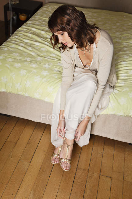 Young elegant woman putting on shoes on bed — Stock Photo
