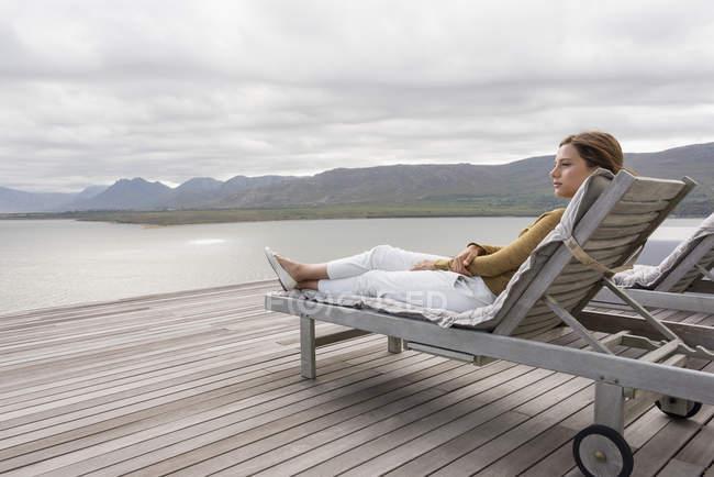 Élégante jeune femme relaxante sur un transat au bord du lac — Photo de stock